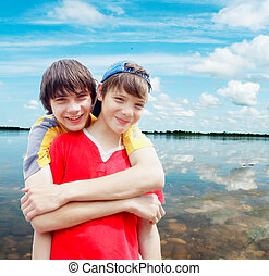 Two teenagers on river bank against the dark blue sky