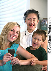 Family enjoying communication from cell texting - A family...