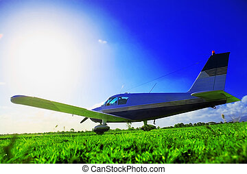 Small plane waiting on grassy field