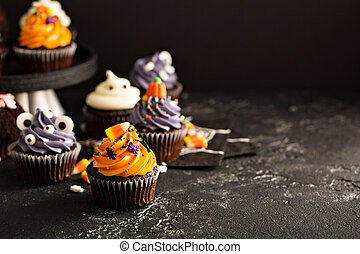 Festive Halloween cupcakes and treats decorated with...