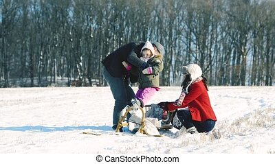 Father and mother with a daughter on a sledge. - Mother and...