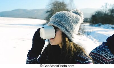 Beautiful young woman with cup of coffee in winter nature. -...