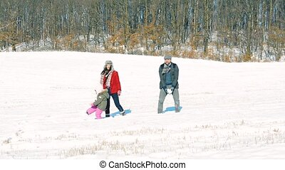 Father and mother with their daughter, playing in the snow....