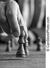 Greyscale image of a businessman playing chess moving black...