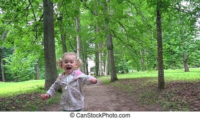 Naughty little girl running through park tree alley in front...