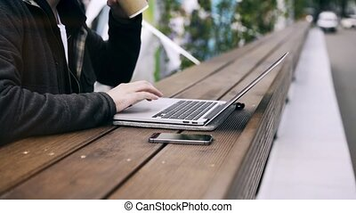 Side view of a man working on his laptop in a park