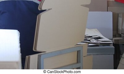 Manufacture of cardboard boxes. - Cutting the cardboard box...