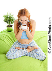 Young woman in yoga pose drinking tea