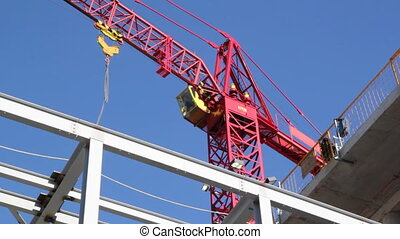 Red tower crane. Medium. - Closeup of red tower crane at...