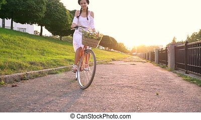Young beautiful woman riding a bicycle at sunset. Video...