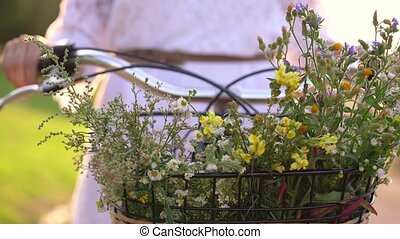 Basket with flowers close-up. Woman standing near her...