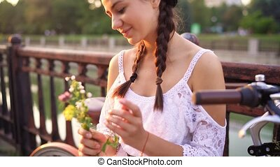 Young beautiful woman sitting on her bicycle with flowers at sunset