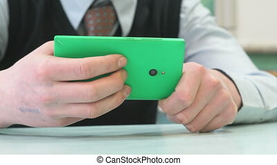 Unknown schoolboy holding green smartphone - Classes at...