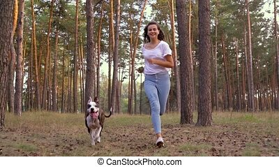 Girl playing with her dog in the forest at sunset. Slow...