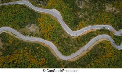 Aerial view of a traffic driving along a mountain road in...