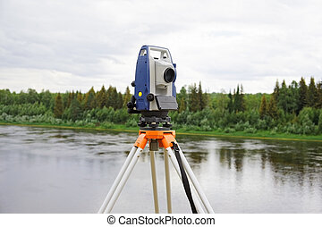 Modern electronic tachymeter mounted on tripod in field...