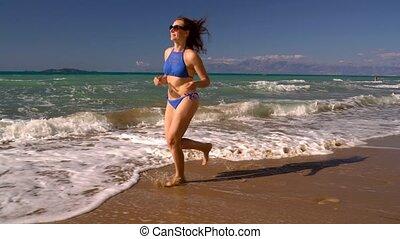 Beach bikini woman carefree running along the water on the...
