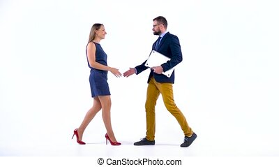 Two business partners shake hands welcoming each other in...
