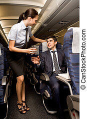 During flight - Kind stewardess giving glass of water to...