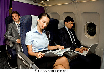 In airplane - Image of pretty girl reading magazine while...