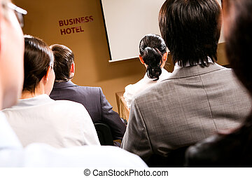 Students - Rear view of business people listening...