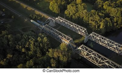 Passenger train goes over the bridge, filming from the top -...