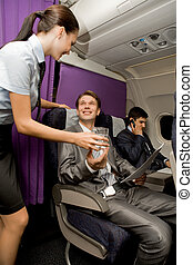 Airplane service - Image of pretty stewardess giving glass...