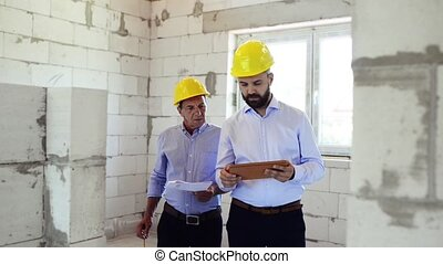 An architect and worker at the construction site. -...