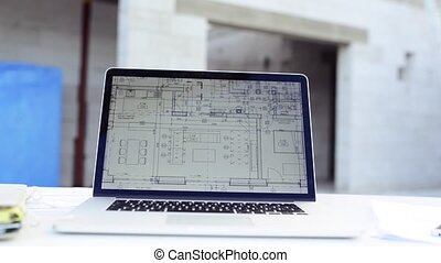 Blueprints and laptop on construction site. - Close up of...