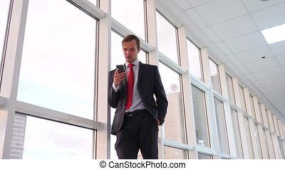 The businessman walk and phone near the panoramic window....