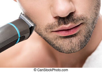 trimmer - young handsome man shaving with electric trimmer...