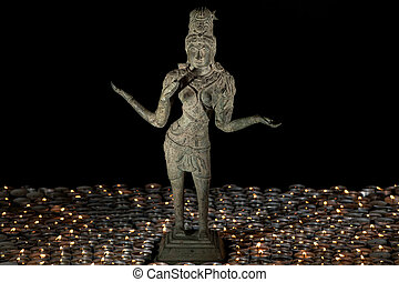 Traditional bronze statue of Lakshmi by candle light. Hindu...