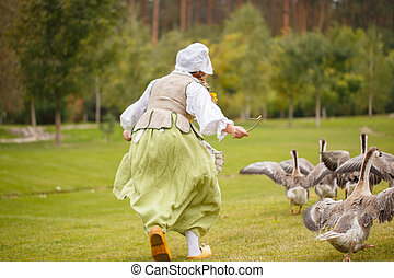 A peasant woman grazes a geese. back view - A peasant woman...