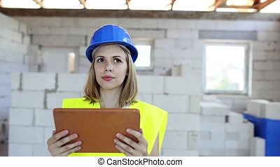 Young woman with tablet at the construction site. Woman...