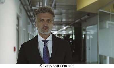 Mature businessman in black suit in the office, walking. -...