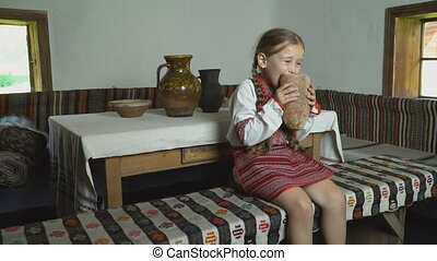 the girl is eating bread sitting in the room