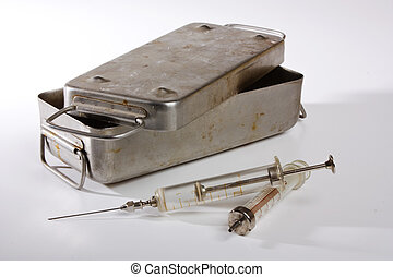 old glass syringe - old medical syringes and a metal box