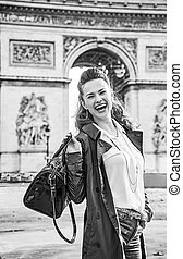 smiling young fashion-monger in trench coat in Paris, France...