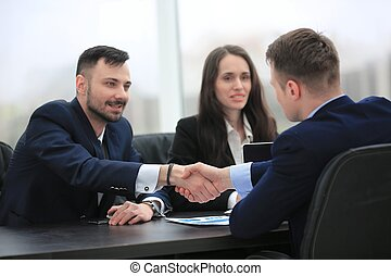 handshake financial partners sitting at the table - concept...