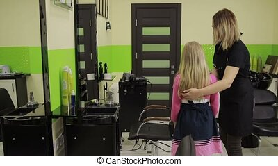 Adorable girl visiting hairstylist in barber shop - Smiling...