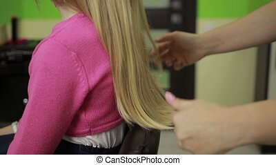 Professional hairstylist arranging child's hair - Closeup...