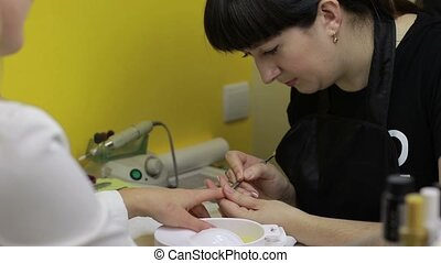 Manucirist doing cuticles care with cuticle pusher -...