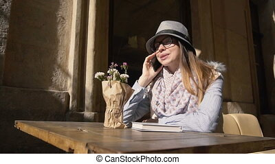 Girl Chats in Outdoor Cafe - Caucasian girl, in grey striped...