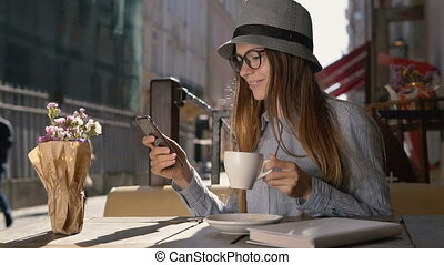 Girl Uses Phone and Enjoys Coffee - Smiling girl, in grey...