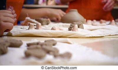 child hands making a clay pottery