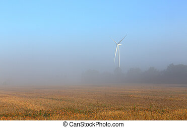 Wind turbine in the mist at dawn in southern Ontario