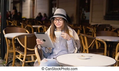 Girl Reads from Tablet in Cafe - Intelligent caucasian girl,...