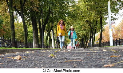 mother and daughter on an empty autumn alley