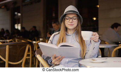 Girl Reads Book during Coffee Time - Beautiful caucasian...