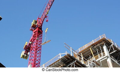 Red crane at work. - Red tower crane at construction site....